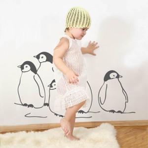 Mädchen vor Pinguintattoo an der Wand